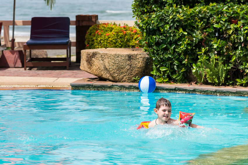 Trat, Thailand - May, 21, 2017 : Unidentified name Boys swimsuit floating and playing with ball in the swimming pool at Klong Prao Resort in Prao Beach Koh Chang island Trat, Thailand. Day Editorial  Floating On Water Fun Illustrative Illustrative Editorial Leisure Activity Lifestyles Looking At Camera Nature One Person Outdoors People Portrait Real People Sea Smiling Summer Swimming Swimming Pool Thailand Tree Vacations Water Young Adult