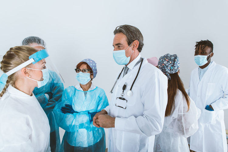 Doctors wearing mask standing against white background