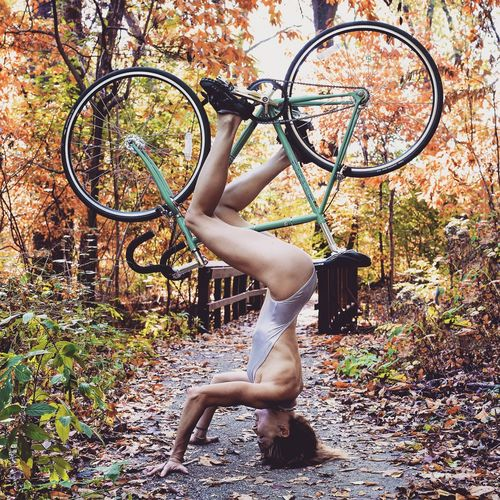 Side View Of Young Woman Performing Headstand With Bicycle At Park