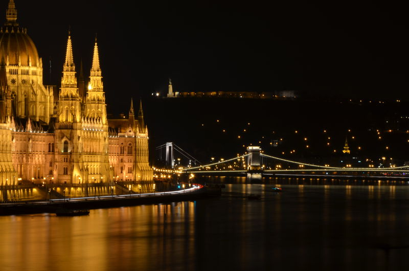Hungarian parliament building by danube river against sky in city at night