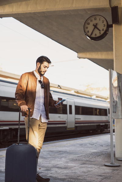 Blue eyed man waiting for the train Adult Man Manhattan Spanish Station Tablet Travel Waiting Waiting In Line Young Attractive Call Cellular Handsome Handsome Boy Male Mammal One Person Phone Rail Railway Smartphone Train Train Station Young Adult