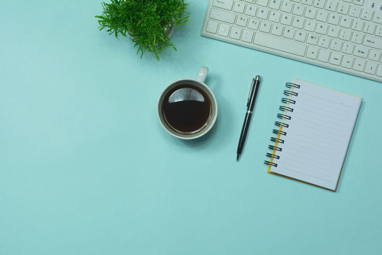 High angle view of coffee with keyboard and plant by note pad on blue table