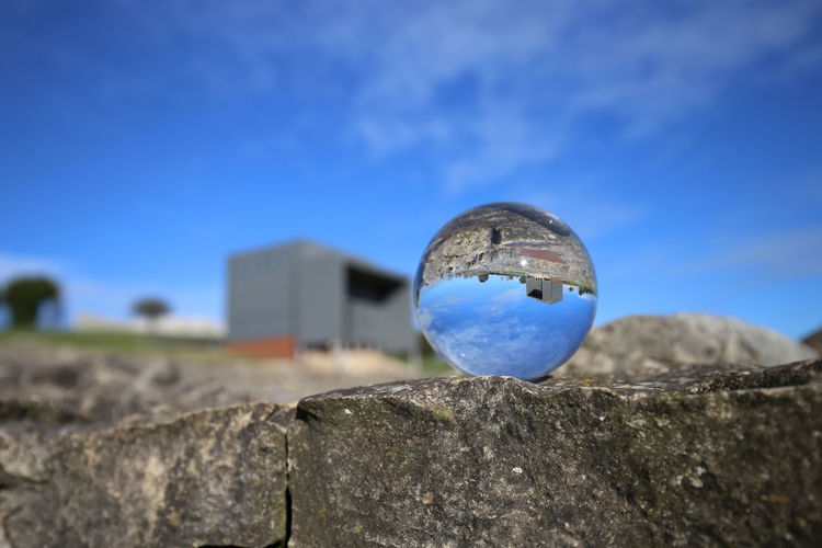 Close-up of blue ball on rock against sky