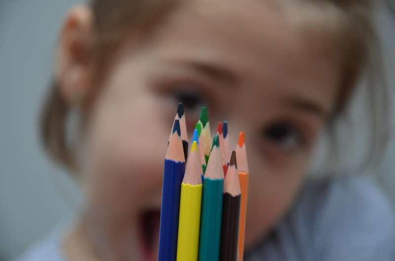 Portrait Of Girl Showing Colored Pencils