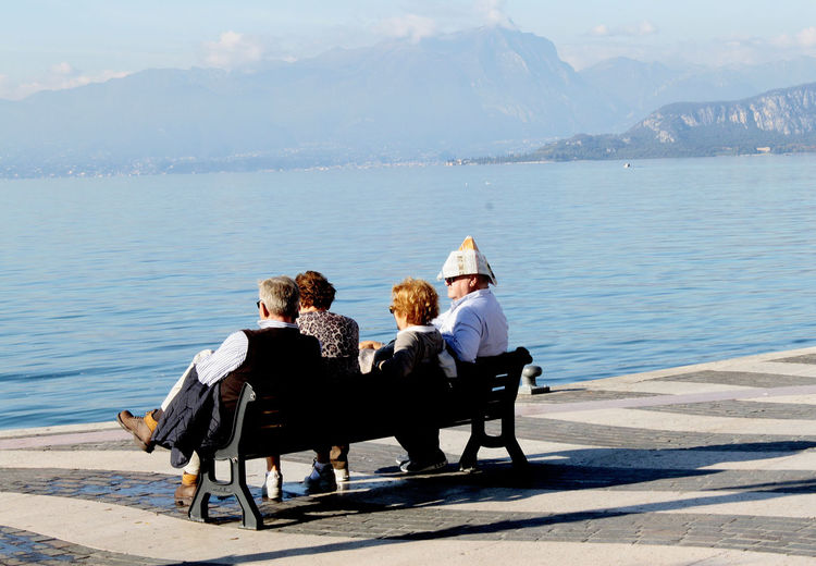 fore guys sitting on a bench, one with a paper hat Autumn Blue Calm Casual Clothing Enjoying Life Freedom Gardasee Happiness Holydays Lago Di Garda Lake Lifestyles Mountain Paper Hat Papierhut People Relaxing Retired Togetherness Tourist Urlaub Vacations Water The Street Photographer - 2017 EyeEm Awards The Street Photographer - 2019 EyeEm Awards
