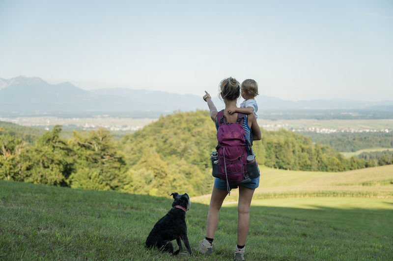 Rear view of woman with dog on field