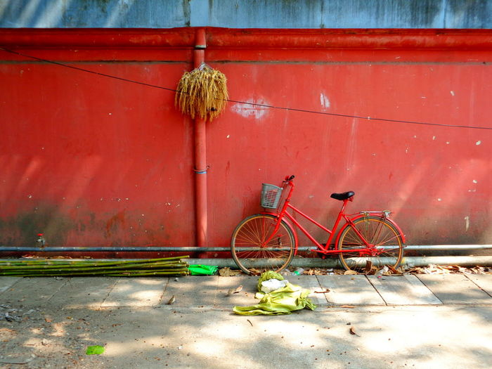 Bicycle parked on sidewalk against wall
