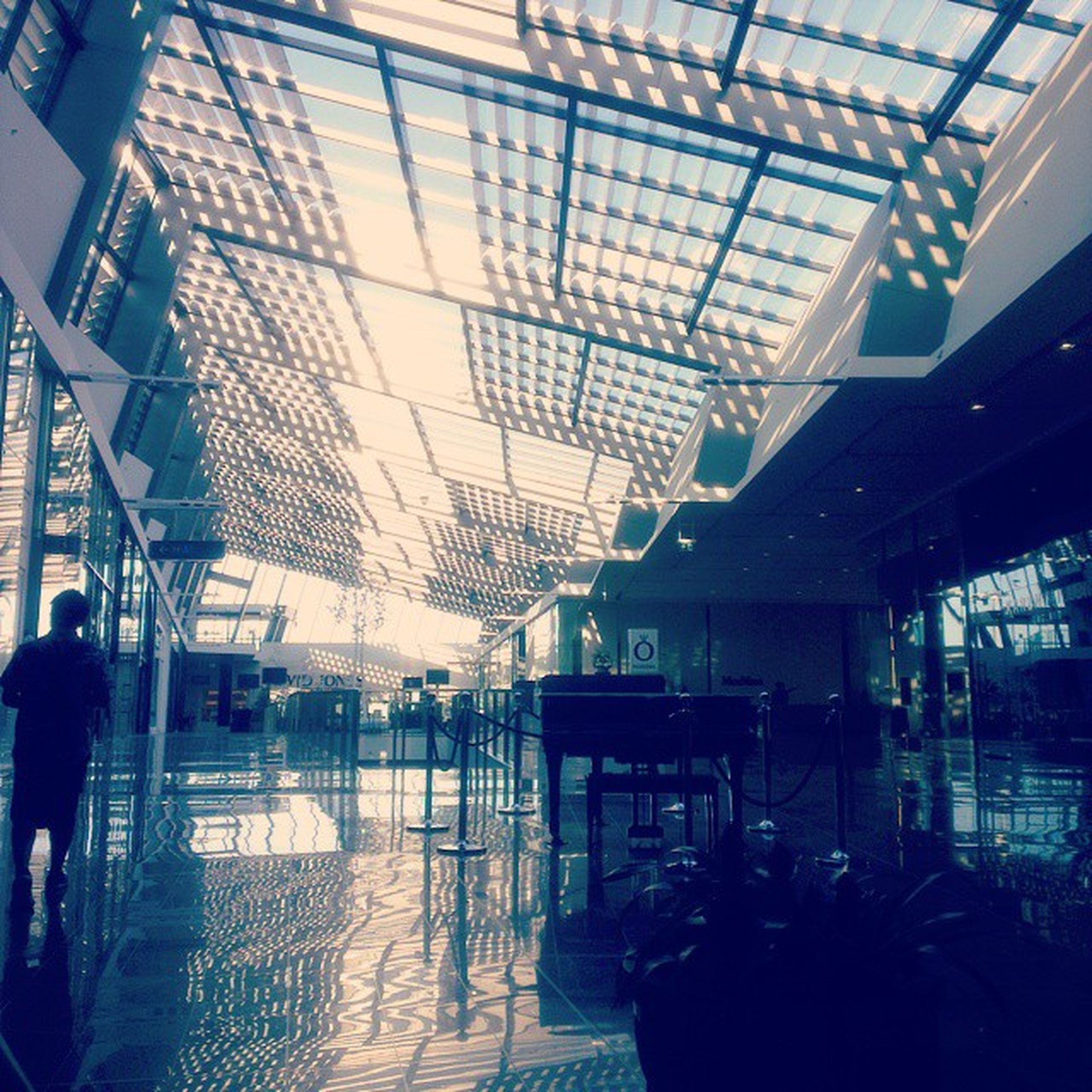 indoors, ceiling, architecture, glass - material, built structure, modern, window, men, transparent, chair, lifestyles, person, incidental people, interior, sunlight, reflection, silhouette, leisure activity, day