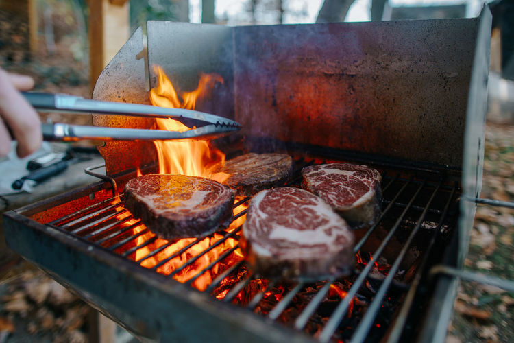 Close-up of hand grilling meat on barbecue grill
