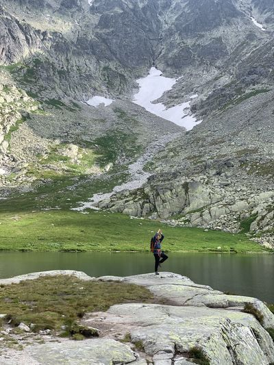 Man standing on rock by lake