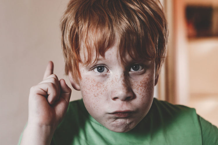Close-up portrait of boy making face at home
