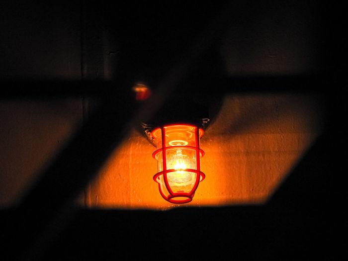 Close-up of illuminated light bulb on wall in darkroom