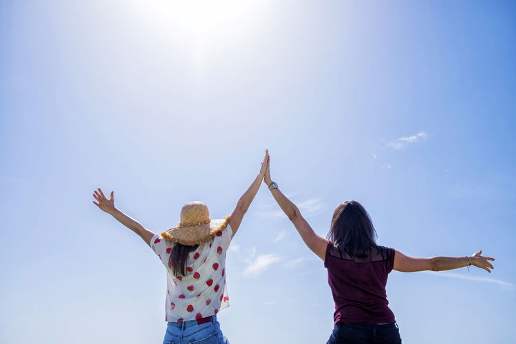 Rear view of two young woman sitting on a fence with arms raised against blue sky Sky Human Arm Togetherness Women Real People Leisure Activity Lifestyles Two People Bonding Standing Casual Clothing Arms Raised Sunlight Adult Limb Arms Outstretched Nature Emotion Friendship Positive Emotion Outdoors Lens Flare Hairstyle Sister