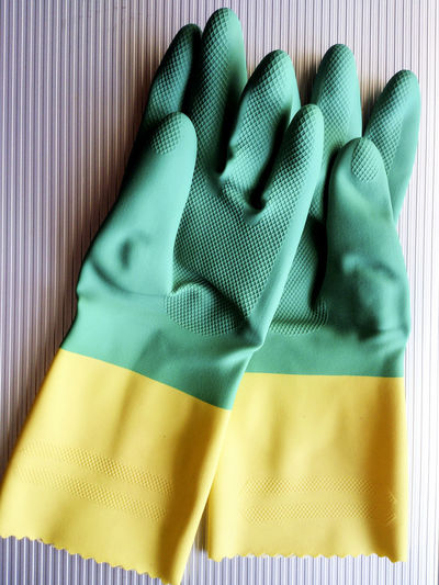 Close-up of green and yellow rubber gloves on table