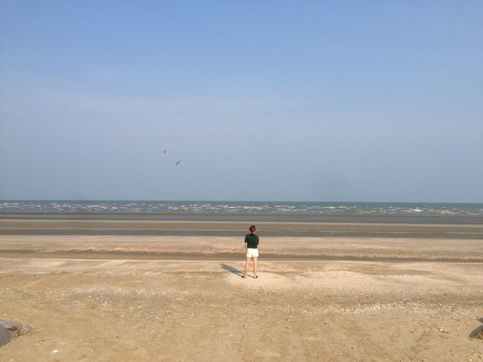 Rear view of woman standing on sea shore against sky