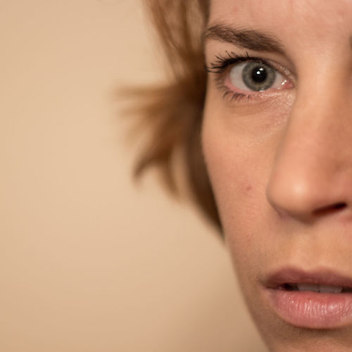 Close-up portrait of woman against beige background