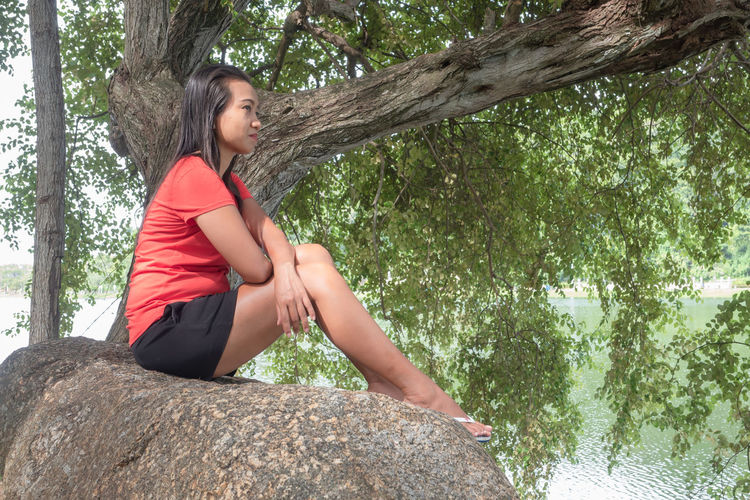 Woman sitting on rock against trees