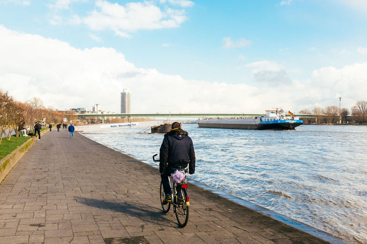 Rear view of man cycling on promenade by rhine river