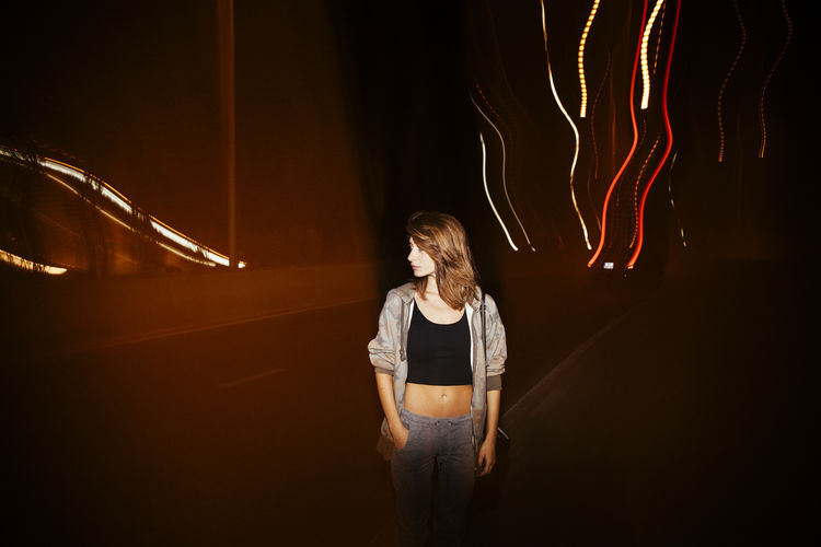Woman looking away while standing against illuminated lights
