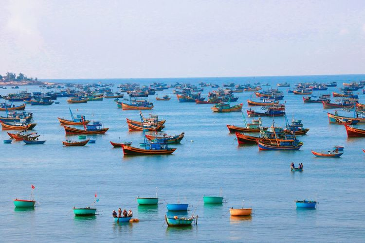Fishing boats anchored on river against clear sky