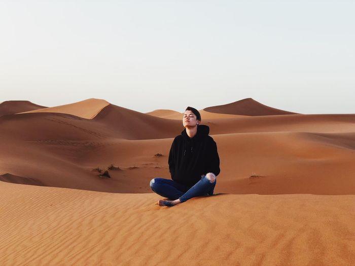 Full length of man sitting on sand dune