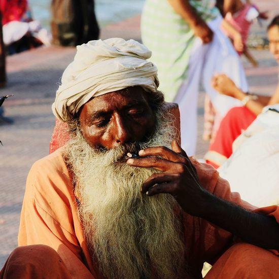 Sadhu smoking cigarette while sitting outdoors