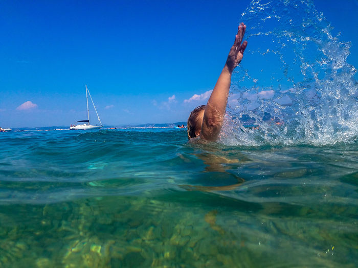 Mid adult woman with hand raised swimming in sea against blue sky during sunny day