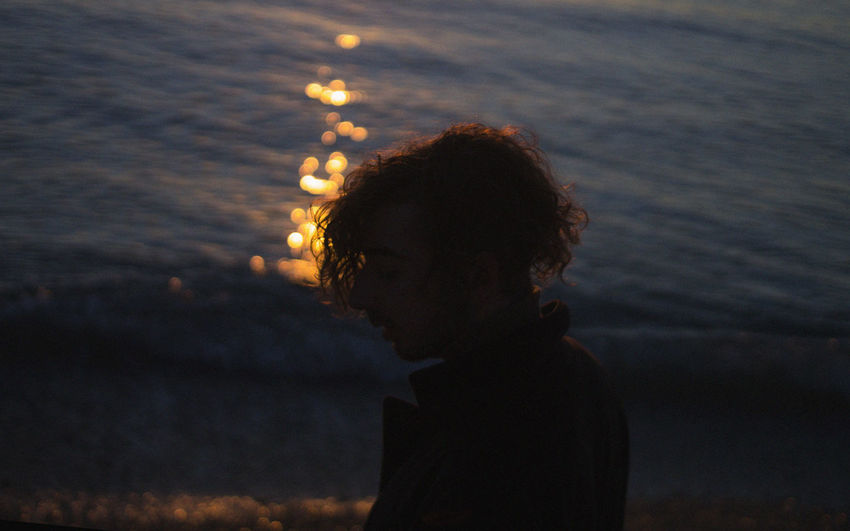 Water Sunset One Person Real People Leisure Activity Lifestyles Focus On Foreground Child Childhood Nature Headshot Sky Portrait Sea Side View Outdoors Standing Hairstyle Contemplation