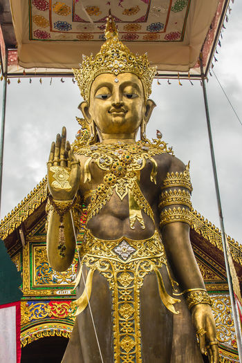 Low angle view of statue against temple building