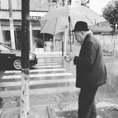 Architecture Blackandwhite Building Exterior Built Structure City Communication Day Downpour Full Length Jaunt Lifestyles Oldman One Person Outdoors Rain Real People Road Standing Street Streetview Stroll SundayBest Theflood Umbrella Young Adult The Street Photographer - 2017 EyeEm Awards
