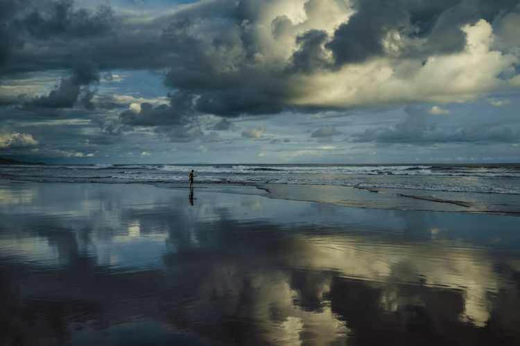 Scenic view of sea with man standing at beach against sky