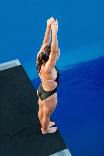 Female Diver On Platform, Preparing To Dive Swimming Diving Arms Up Athlete Diving Board High Individual Sports Standing Water Sport Woman Above Blue Dive Female High Angle View Muscular Build One Person Outdoors Pool Sport Strength Swimming Pool Water Young Adult Young Women