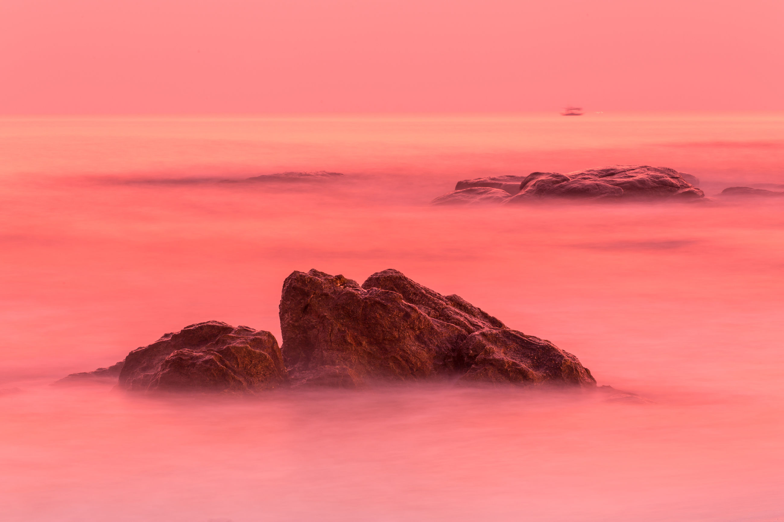 ROCK FORMATION IN SEA AGAINST ROMANTIC SKY