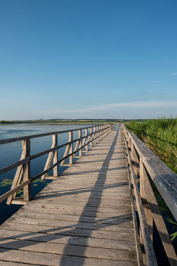 View of wooden bridge over a lake against clear blue sky