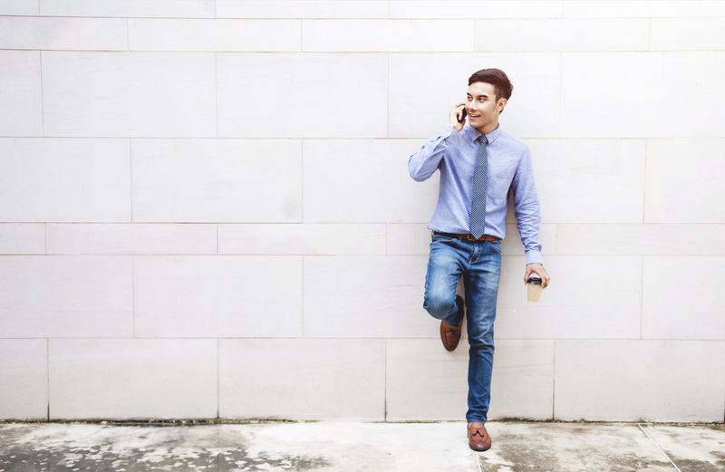Businessman talking on mobile phone while leaning on wall