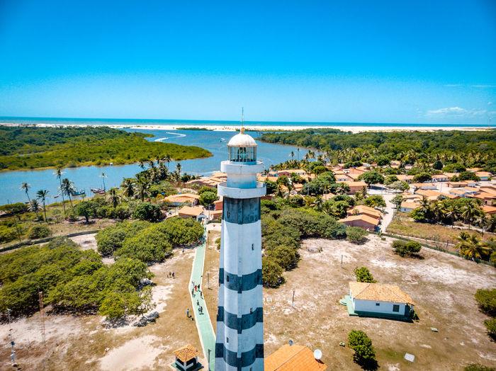Lighthouse amidst plants and buildings against clear blue sky