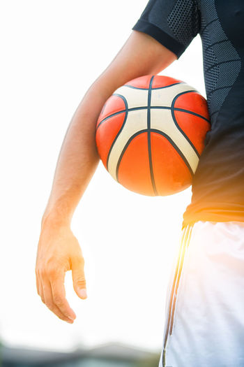 Midsection of man with basketball on waist against sunbeam