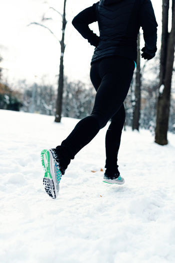 Low Section Of Woman Running On Snow Covered Field