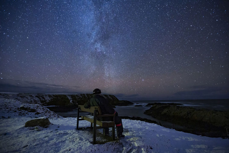 Rear view of man sitting on bench against sky at night