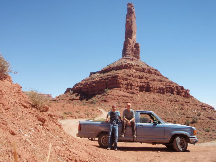 Men Relaxing By Pick-Up Truck Against Rock Formation