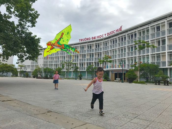 Playing ground Kite Playing Time Fun Skies Playing Kids Child Childhood Architecture Built Structure Cloud - Sky Women Sky Real People Building Exterior Nature Leisure Activity Lifestyles Day Boys Girls Plant Full Length Males