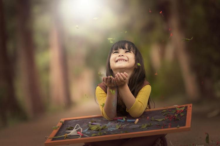 Portrait of happy girl looking away outdoors