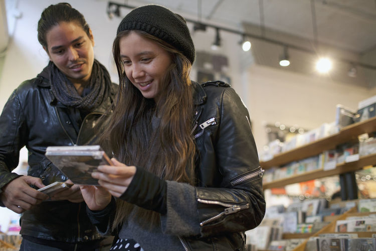 Young woman holding smart phone while standing in store