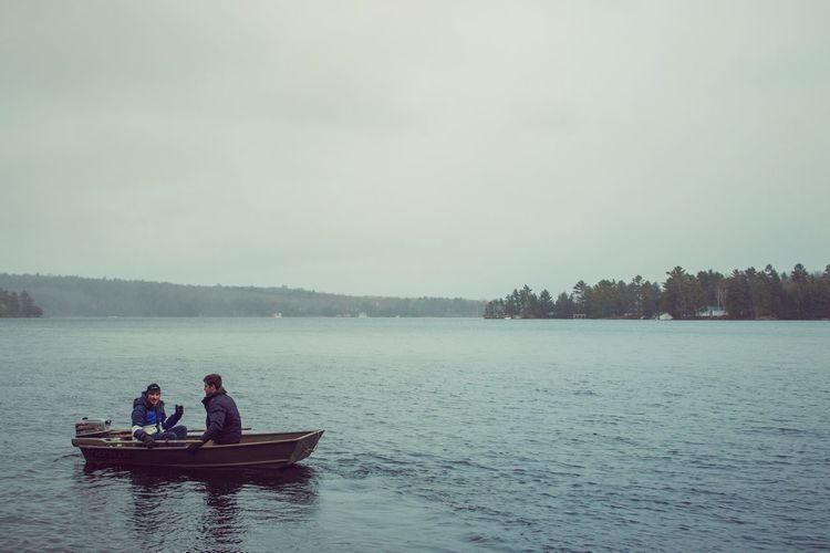 Men sitting in boat against sky