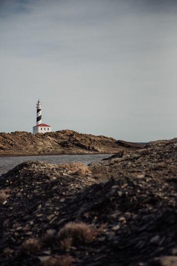 Lighthouse on beach against clear sky