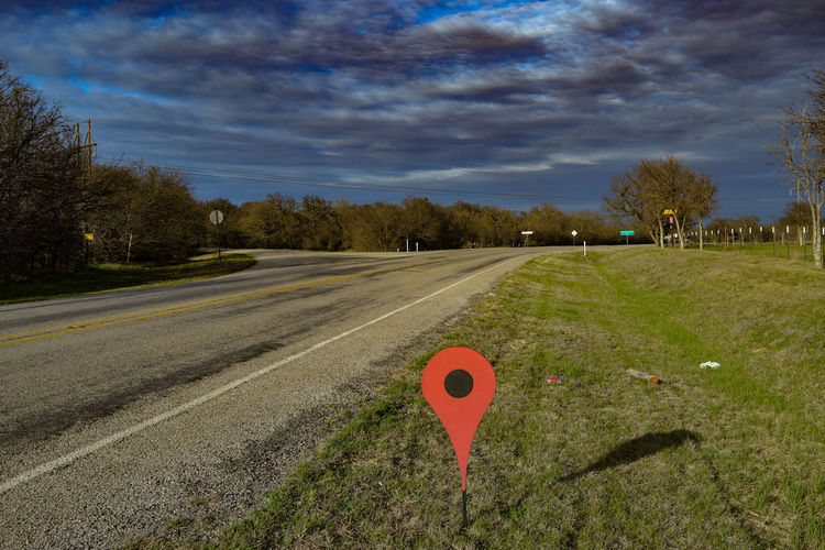 Pointer stick on grassy field by empty road against sky