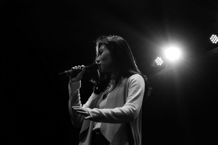 Low angle view of woman with microphone singing in concert