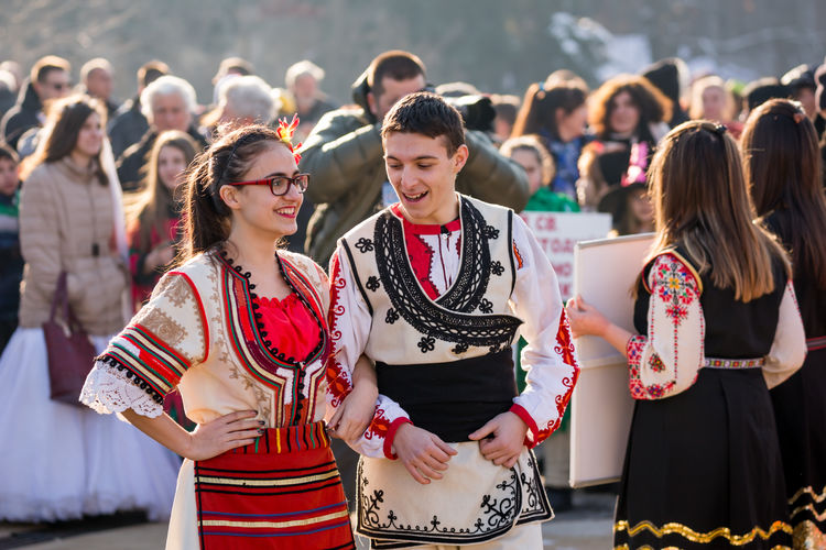 PERNIK, BULGARIA - JANUARY 26, 2018: Two dancers in Bulgarian folk costumes, girl and boy talk and prepare for traditional round dance at the annual International Festival of Masquerade Games Surva Event Games Kukeri Kukeri, Bulgaria Arts Culture And Entertainment Celebration Celebration Event Crowd Day Enjoyment Festival Focus On Foreground Happiness Large Group Of People Leisure Activity Lifestyles Masquerade Music Outdoors People Performance Real People Smiling Standing Surva Togetherness Traditional Clothing Women Young Adult Young Women