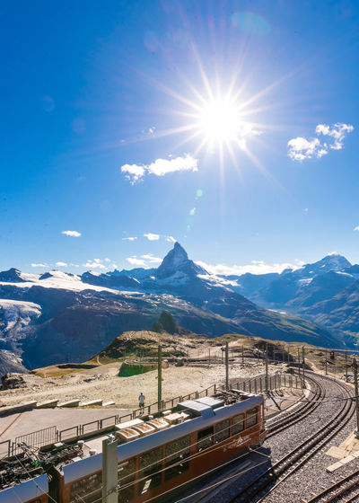 Architecture Beauty In Nature Bright Day Lens Flare Mode Of Transportation Mountain Mountain Range Nature No People Outdoors Rail Transportation Railroad Track Road Scenics - Nature Sky Snow Snowcapped Mountain Sun Sunbeam Sunlight Track Transportation Travel Winter