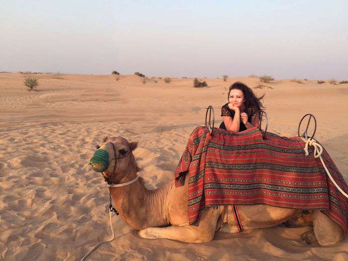 Close-up of woman with camel in desert